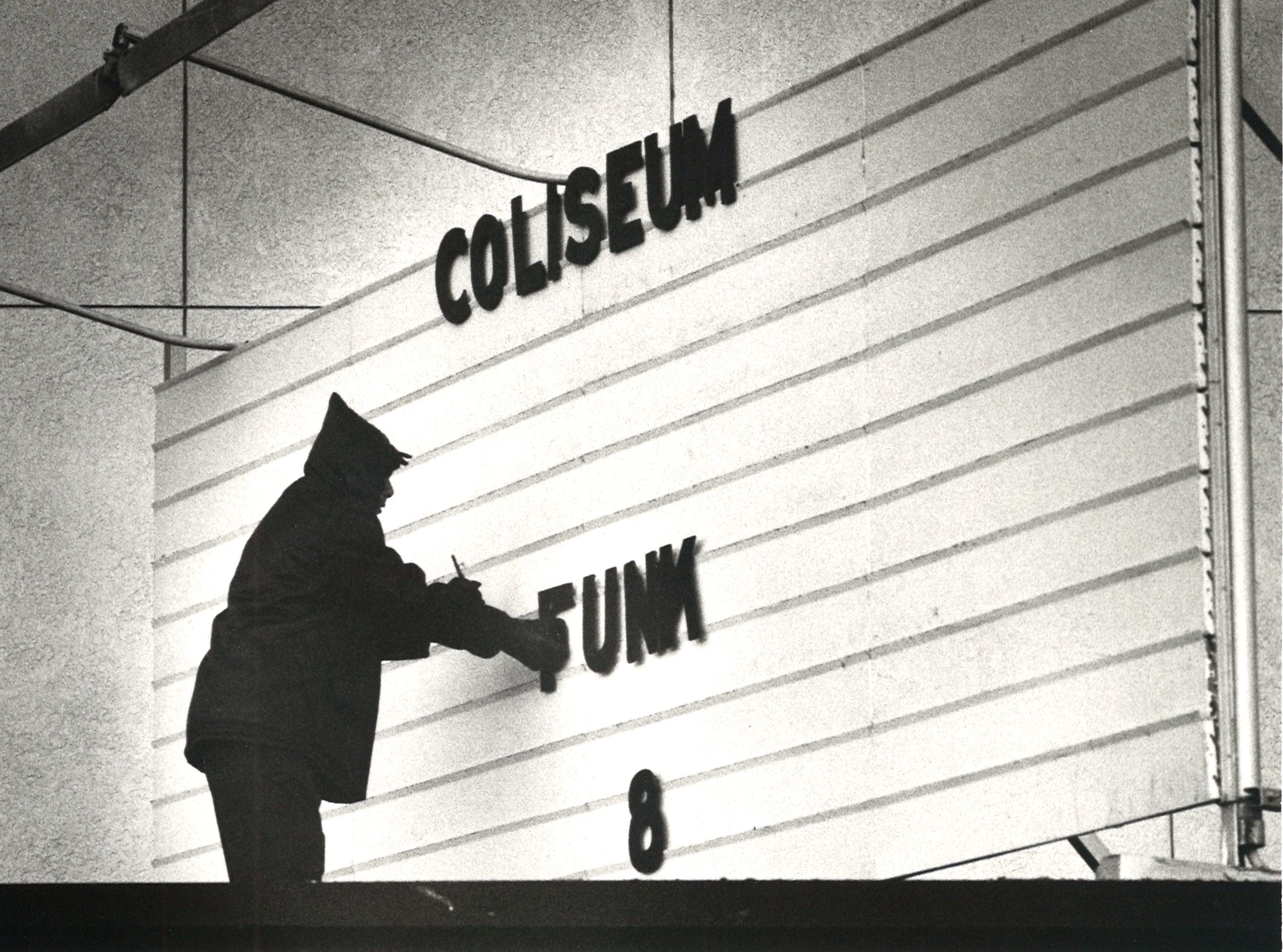 Corpus Christi Memorial Coliseum worker Domingo Nanez removes the letters from the coliseum's marquee on Dec. 18, 1981
