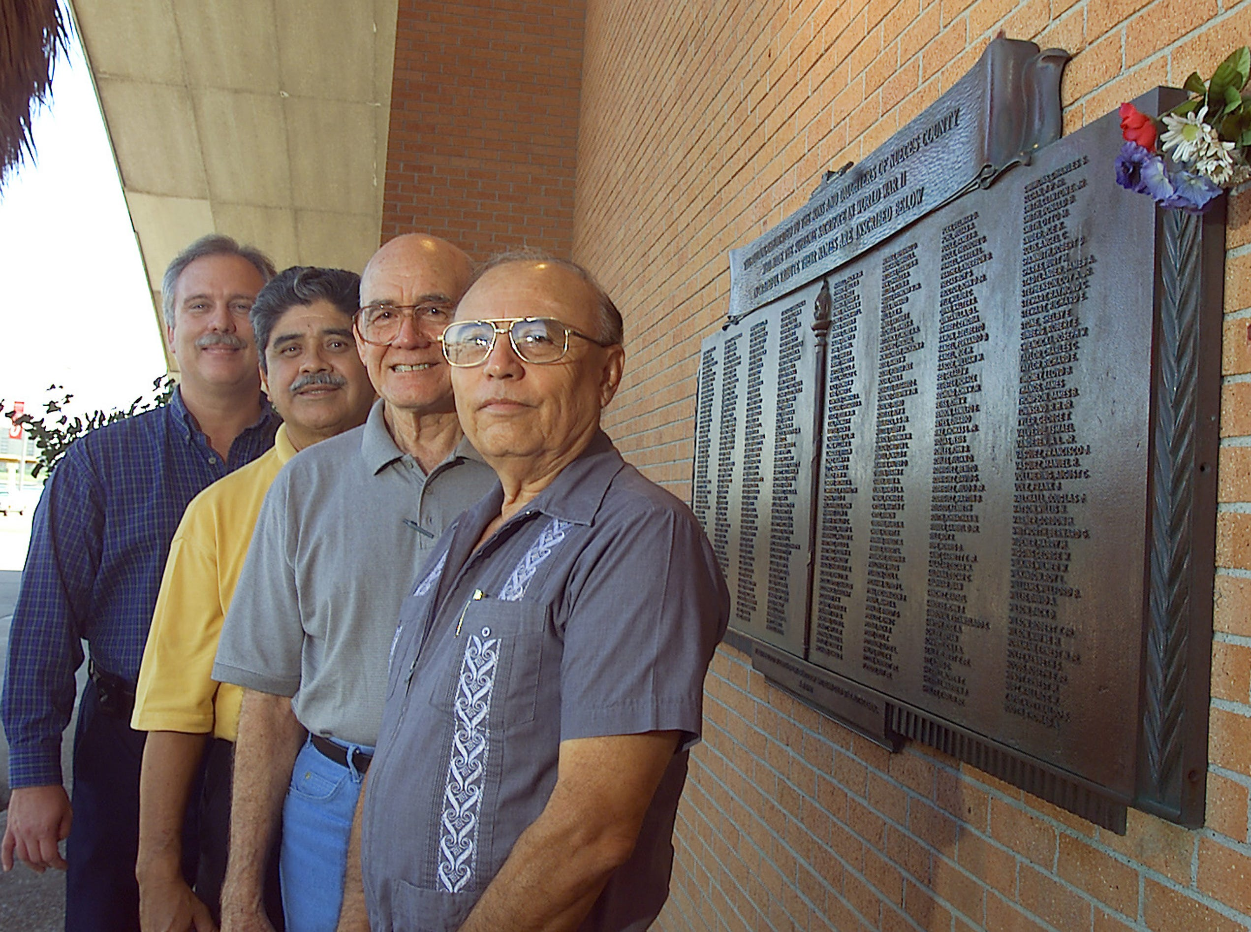 (LT TO RT) Coliseum manager, John Simon, Arturo Casillas, Eli Escobar, Ruben Chavez, at the WWII memorial plaque on the the front wall of Memorial Coliseum on Sept. 27, 2001. The plaque is now in Sherrill Park.