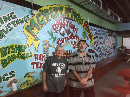 MG's Pizza owner Melody Garver, left, and artist Jessie Flores pose in front of a 75-foot mural that has area high schools represented on Tuesday, January 29, 2019.