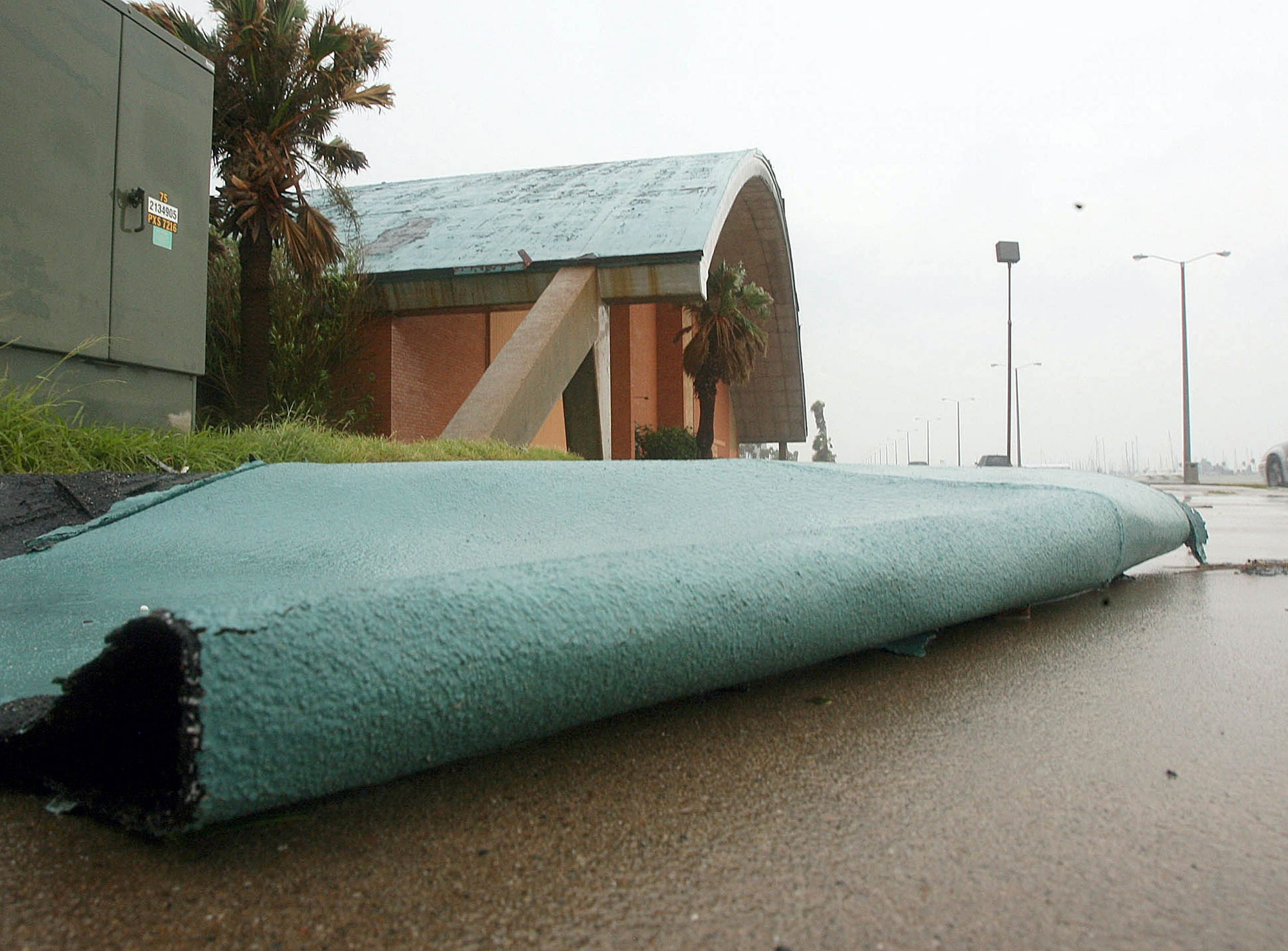 Pieces of the Memorial Coliseum lay about the sidewalk along Shoreline Boulevard after being ripped from the roof of the coliseum by high winds Thursday, July 24, 2008. The high winds were generated by Hurricane Dolly Wednesday, which was down graded to tropical storm.