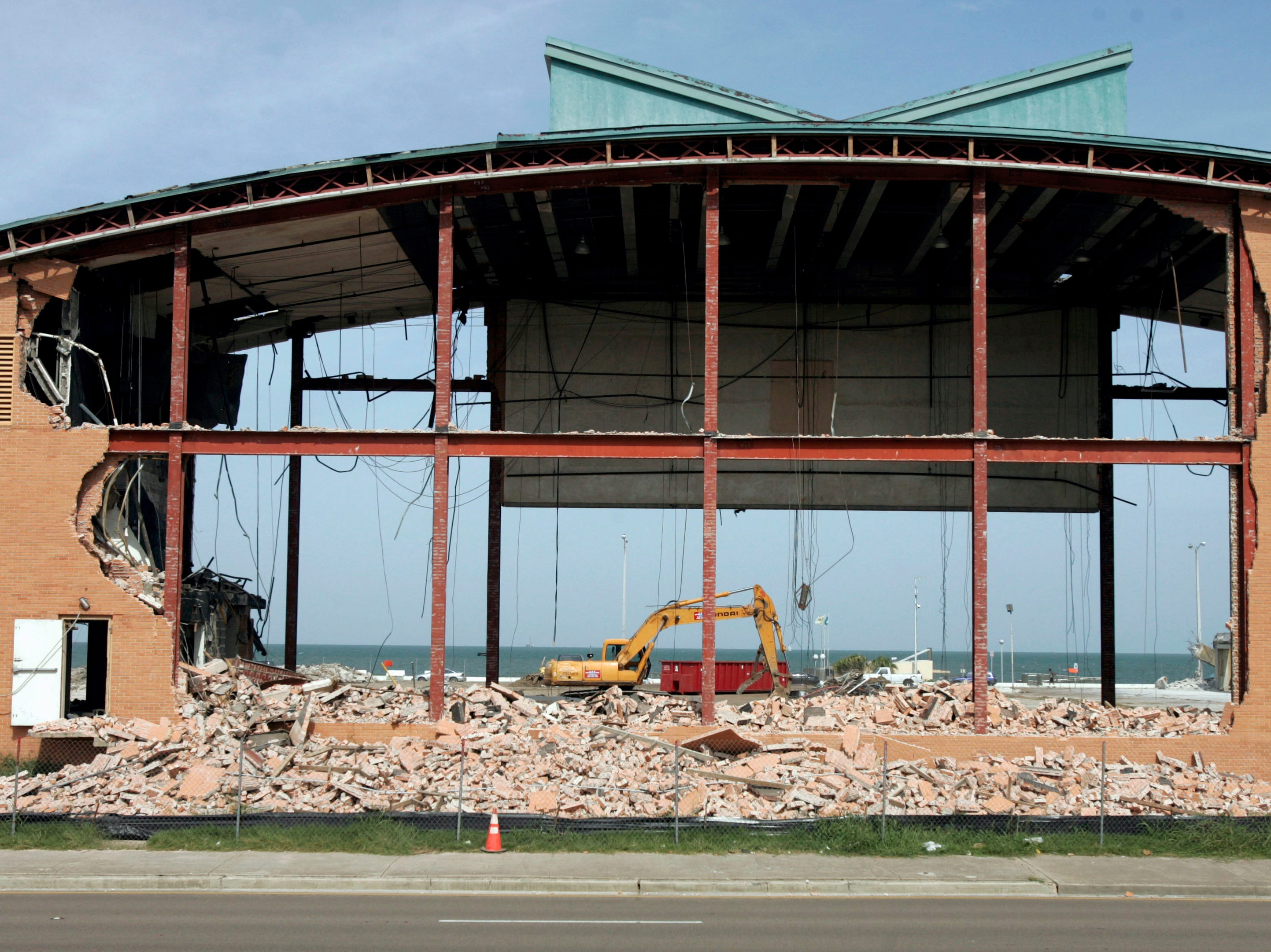 The bay starts to appear Friday, July 16, 2010 as the final wall of Memorial Coliseum starts to come down in Corpus Christi. Before demolition began, the city asked crews to save an 18-by-10-foot piece of a brick wall, pallets of bricks, a piece of the roof and marble slabs. The saved bricks was expected to come from the back side of the coliseum since it had the largest continous piece of wall.