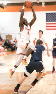 Cherokee's Olare Oladipo puts up a shot over Eastern's Andrew Heck during the 1st quarter of the boys basketball game played at Cherokee High School on Tuesday, January 29, 2019.  Cherokee defeated Eastern, 56-52.
