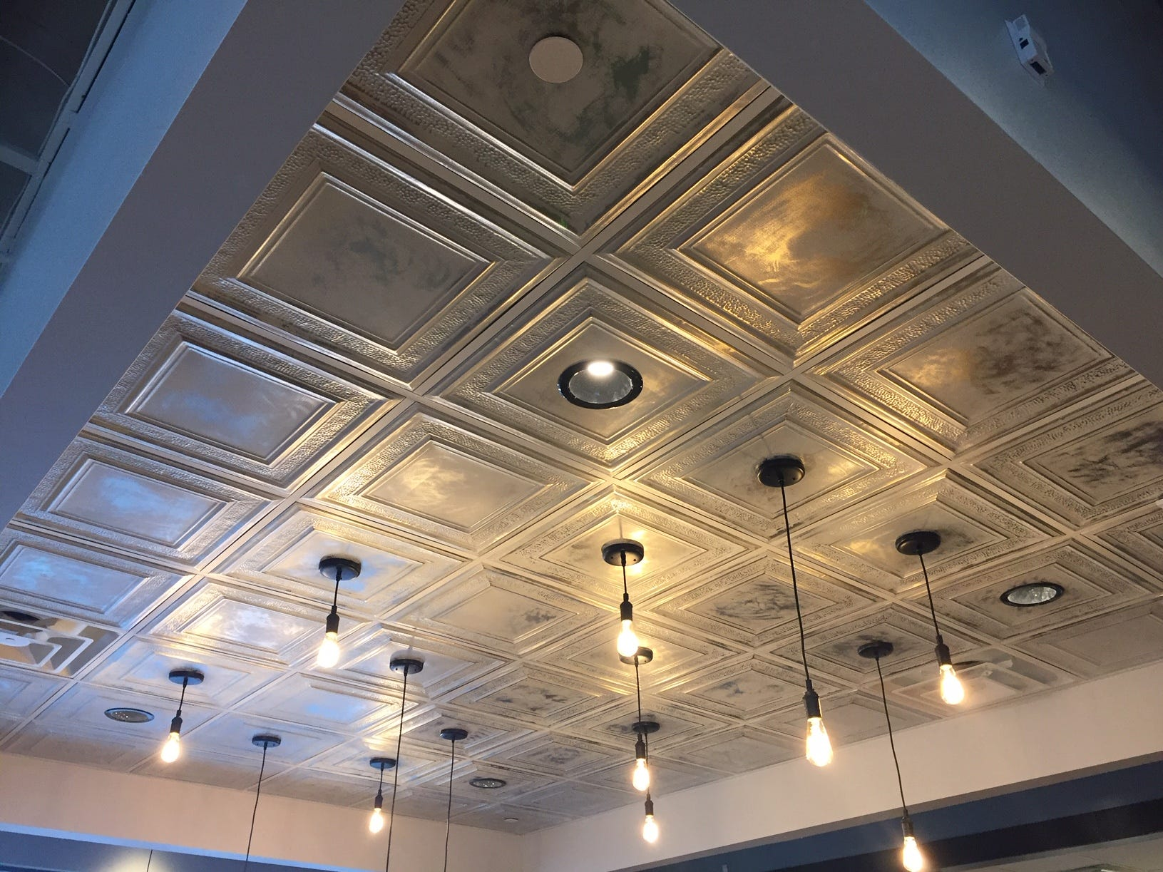 A recessed ceiling and Edison lights provide visual interest to a section of First Watch in Cherry Hill.