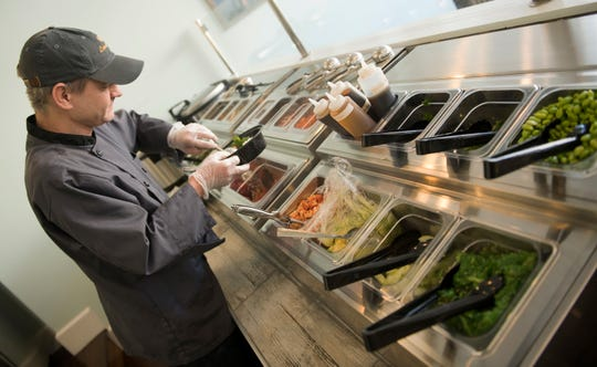 Chef Barry Davis prepares a poke bowl at Aloha Poke Bowl in Collingswood.