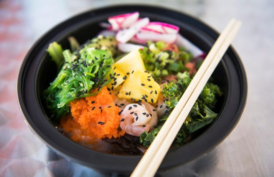 A poke bowl containing sticky rice, kale salad, avocado, spicy tuna, shrimp, pineapple, radish, and masago is displayed at Aloha Poke Bowl in Collingswood.