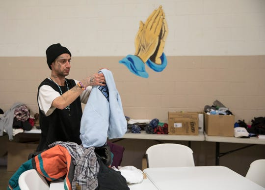 New to the Jefferson Avenue Church of Christ in Christian Union shelter, Thomas Baker tries on a couple hoodies donated to the church to help the homeless during the subzero temperatures affecting the local population and businesses in Chillicothe.