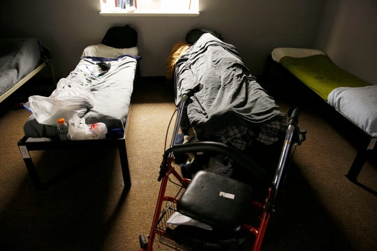 A person sleeps at the Emergency Shelter of Northern Kentucky in Covington, in January 2019. The shelter also provides hot meals and showers. Emergency cold shelters have opened across the Greater Cincinnati as the wind chill has reached 20 below zero in parts of the area.