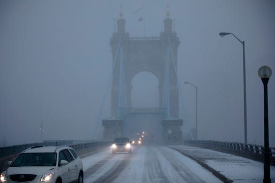 Cars drive across the Roebling Bridge during a snow storm on Wednesday, Jan. 30, 2019, in Downtown Cincinnati. The extreme cold and record-breaking temperatures are moving through Ohio from a storm that pounded Missouri earlier this week. The National Weather Service has issued a wind chill advisory for the Cincinnati Area. The wind chill is currently -17 degrees Fahrenheit.