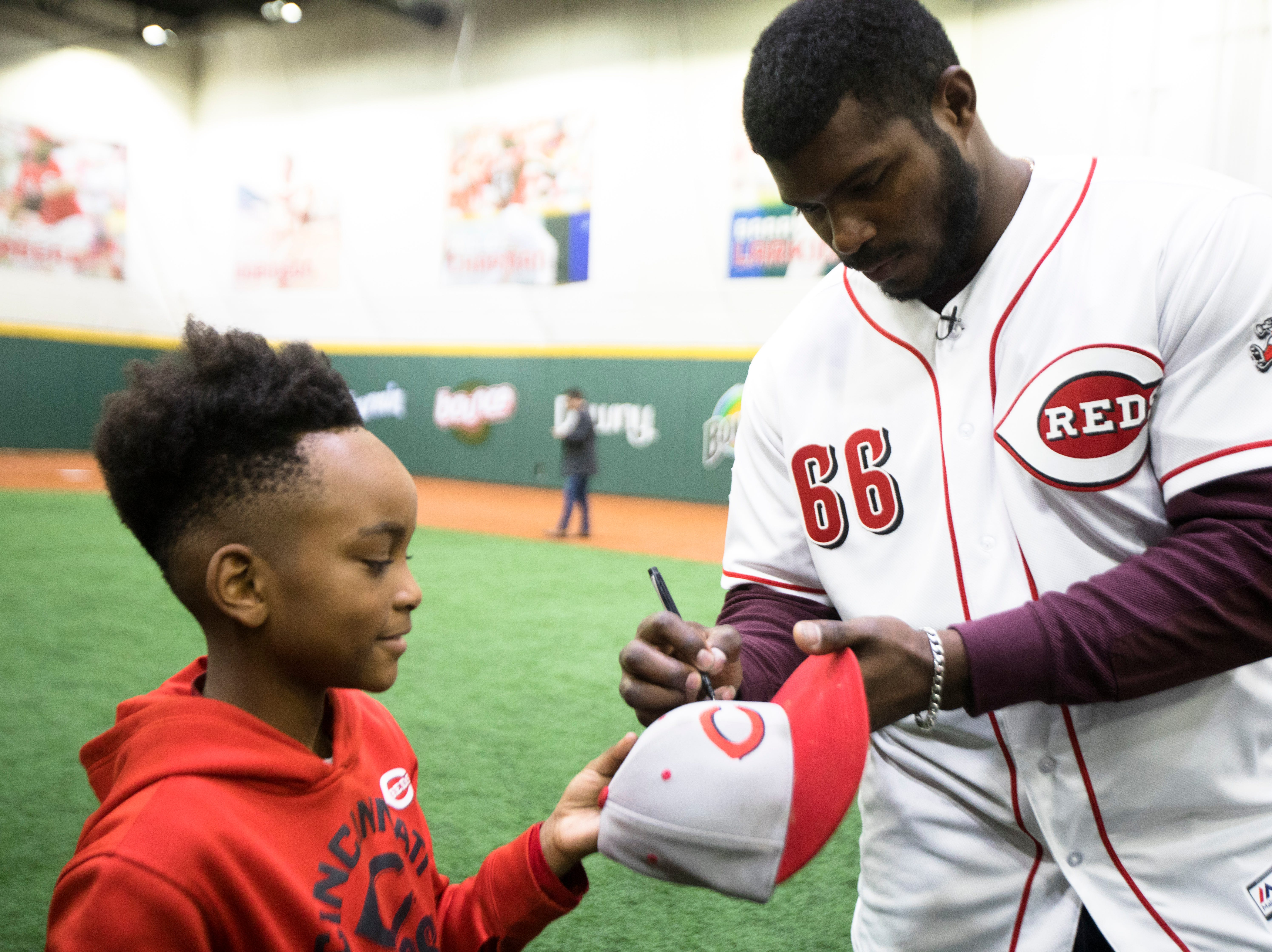 Yasiel Puig, who has been traded to the Cincinnati Reds from the LA Dodgers, signs a hat for a young athlete the P&G MLB Cincinnati Reds Youth Academy on Wednesday, Jan. 30, 2019.
