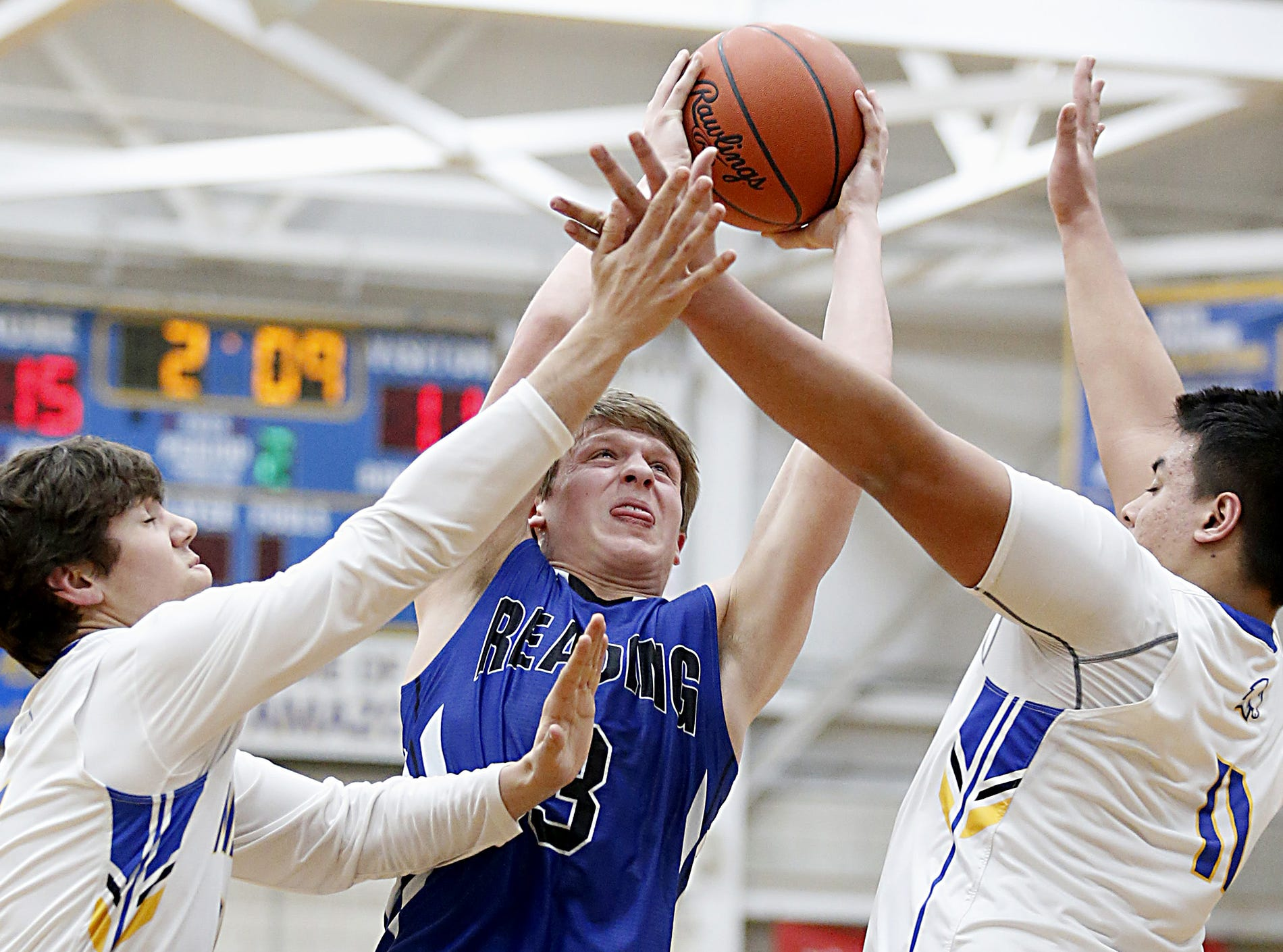 Reading forward Gabe Van Skaik fails to score while covered by Madeira forward Gray Palmer and center Eric Hoeffel during their game at Madeira Tuesday, Jan. 29, 2019.