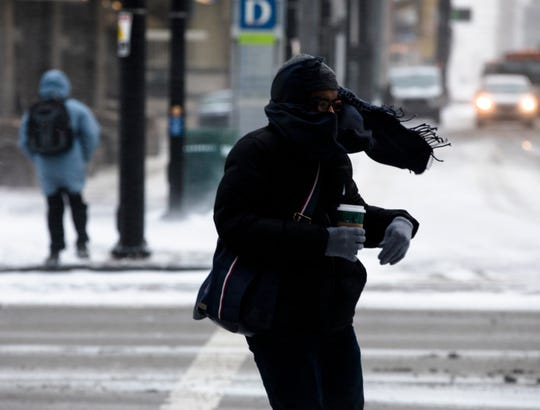 A Pedestrian walks through a winter storm on Wednesday, Jan. 30, 2019, in Downtown Cincinnati. The extreme cold and record-breaking temperatures are moving through Ohio from a storm that pounded Missouri earlier this week. The National Weather Service has issued a wind chill advisory for the Cincinnati Area. The wind chill is currently -17 degrees Fahrenheit.