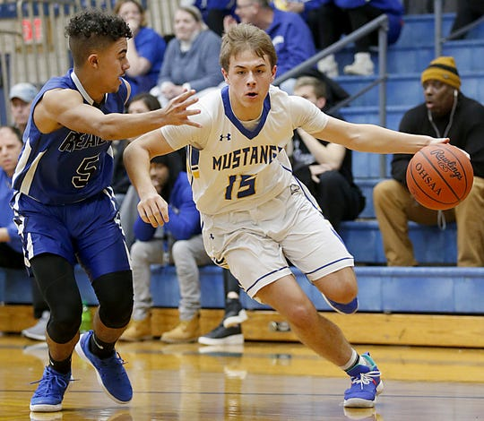 Madeira guard Cameron Finke tries to drive past Reading guard Allijah Vaught during their game at Madeira Tuesday, Jan. 29, 2019.
