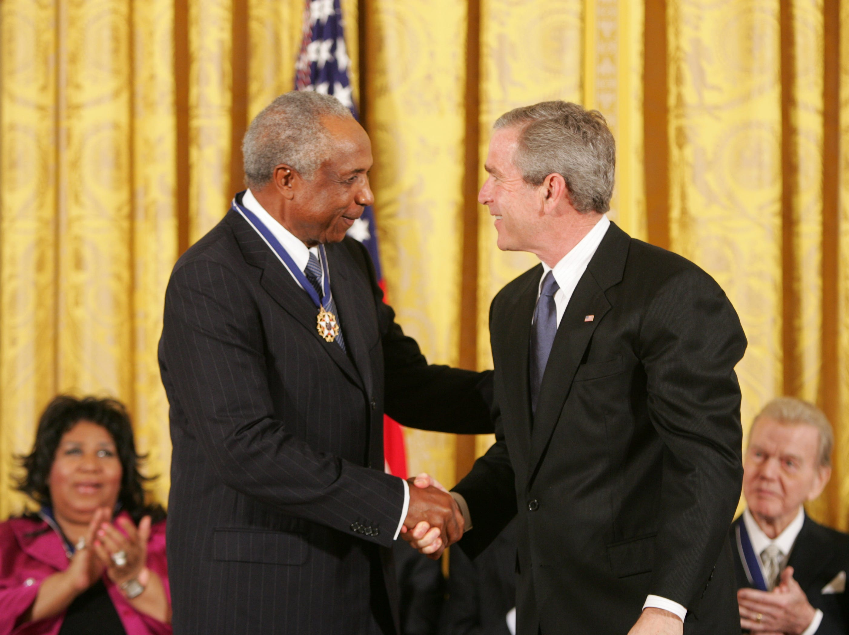 President George W. Bush presents the Presidential Medal of Freedom to baseball legend Frank Robinson in the East Room Wednesday, Nov. 9, 2005. Winning the Most Valuable Player awards in the National and American Leagues, he achieved the American League Triple Crown in 1966. Mr. Robinson became baseball's first African-American manager.