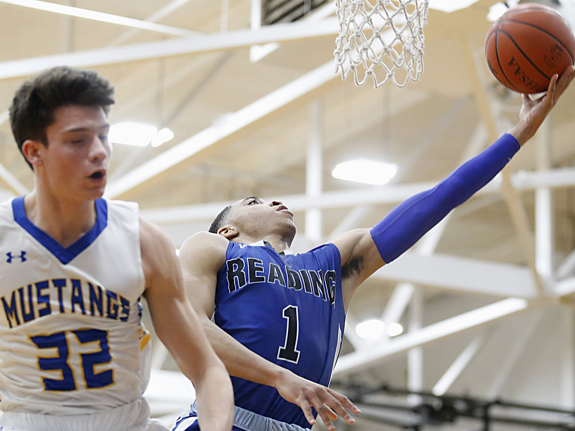 Reading guard A.J. Brown puts up two as Madeira forward James Lytle sails past during their game at Madeira Tuesday, Jan. 29, 2019.