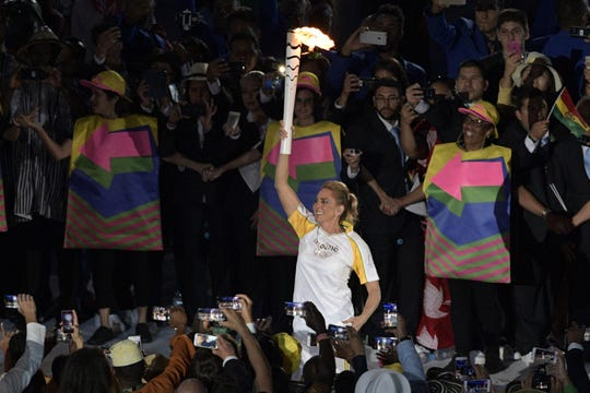 Brazilian basketball icon Hortencia Marcari carries the Olympic flame during the opening ceremony of the Rio 2016 Olympic Games on Aug. 5, 2016.
