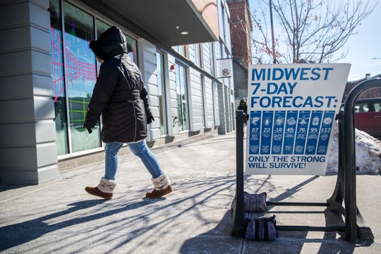 A woman bundled in a coat and boots walks into the East Village store Raygun, past their sign poking fun at midwestern weather on Wednesday, Jan. 30, 2019, in Des Moines. The National Weather Service reported a new record low temperature of -19 in Des Moines on Wednesday morning.