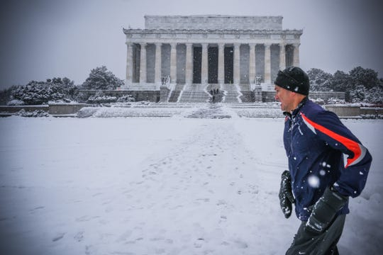 A jogger runs by the Lincoln Memorial as snow accumulates in Washington, D.C., on Jan. 13.