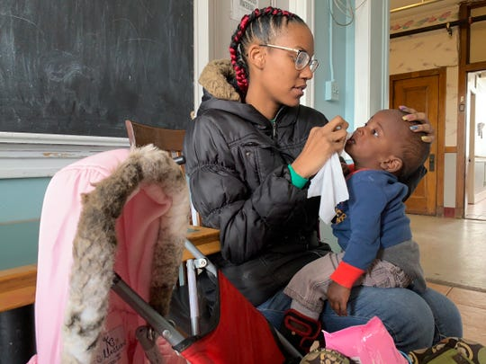 Teri-Ashli Coe, 23, wipes her son's, John, 1, face before sitting down for lunch at Genesis House III, a women and children shelter run by Detroit Rescue Mission Ministries in Detroit on Wednesday, Jan. 30, 2018.