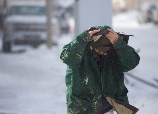 A man bundles up from the cold while walking in downtown Flint on Wednesday, January 30, 2019 on Flint's east side.
