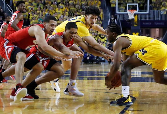 Michigan guard Zavier Simpson, right, steals the ball away from Ohio State forward Jaedon LeDee, center left, during the first half of an NCAA college basketball game Tuesday, Jan. 29, 2019, in Ann Arbor, Mich.