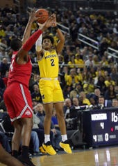 Michigan guard Jordan Poole scores against Ohio State forward Kaleb Wesson during first half action Tuesday, January 29, 2019 at the Crisler Center in Ann Arbor, Mich.