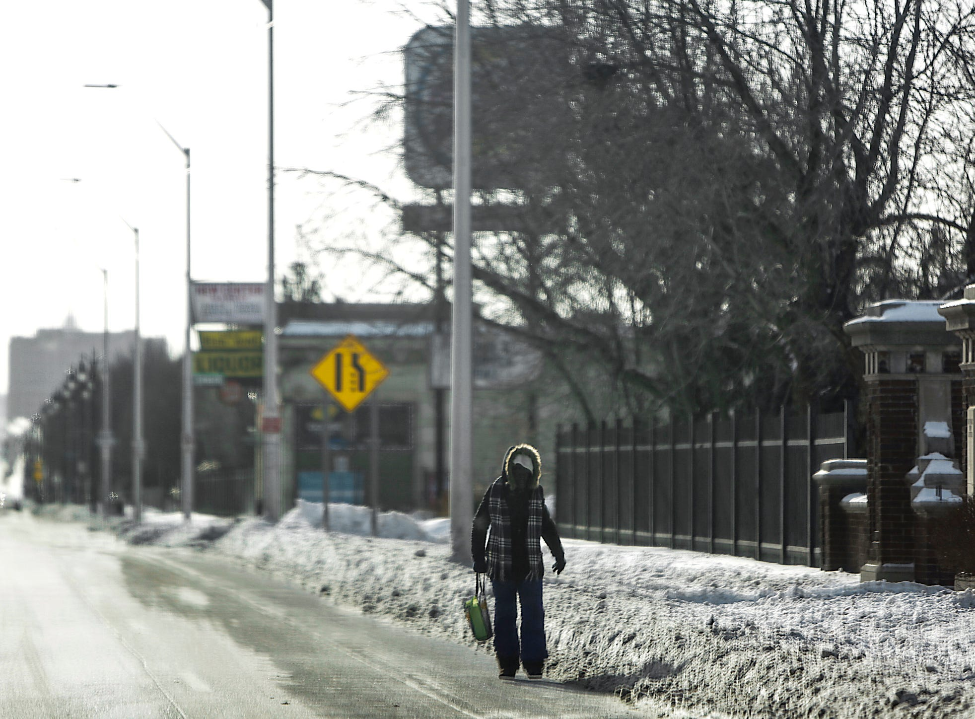A woman walks in the street to avoid the snow-covered sidewalk, during subzero temperatures in Highland Park, Mich. on Wednesday, Jan. 30, 2018.