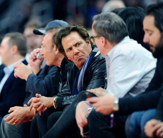 Pistons' owner Tom Gores, center, chats with a fan in the first quarter.