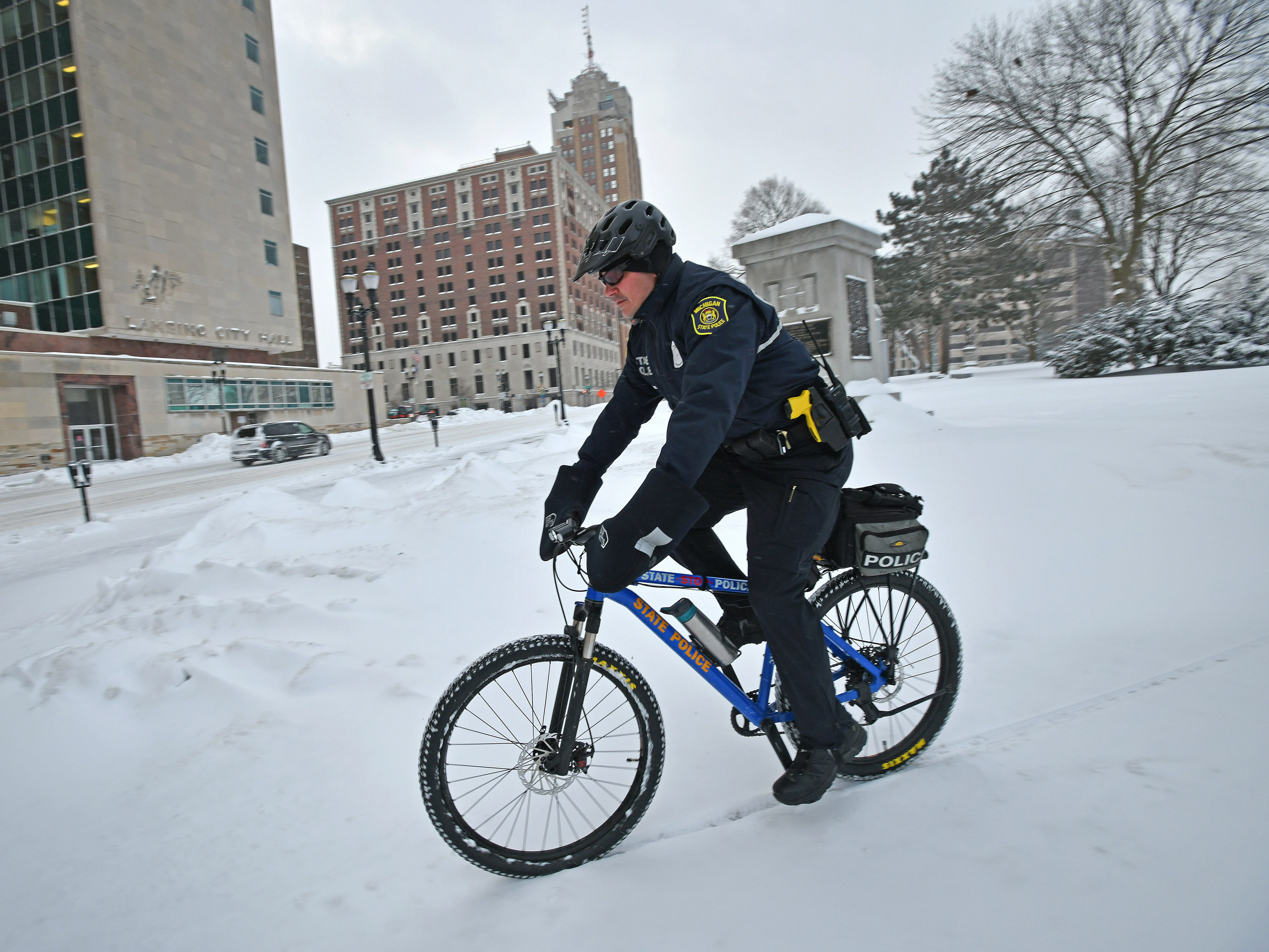 Michigan State Police officer Jeremy Nunez pedals through the drifts in front of the state Capitol on Wednesday morning. Although state government is shut because of the weather, the MSP is still responsible for patrols.