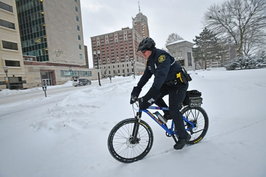 Michigan State Police officer Jeremy Nunez pedals through the drifts in front of the state Capitol on Wednesday morning. Although state government is shut-down because of the weather, the MSP are still responsible for patrols.
