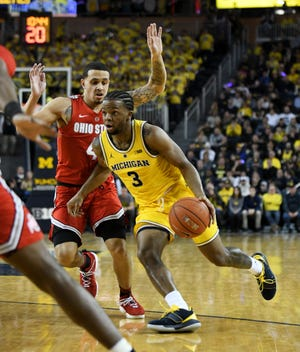 Michigan guard Zavier Simpson (3) drives on Ohio State guard Duane Washington Jr. (4) in the second half. Simpson finished with a triple-double (11 points, 12 assists, 10 rebounds) in UM's 65-49 win Tuesday.