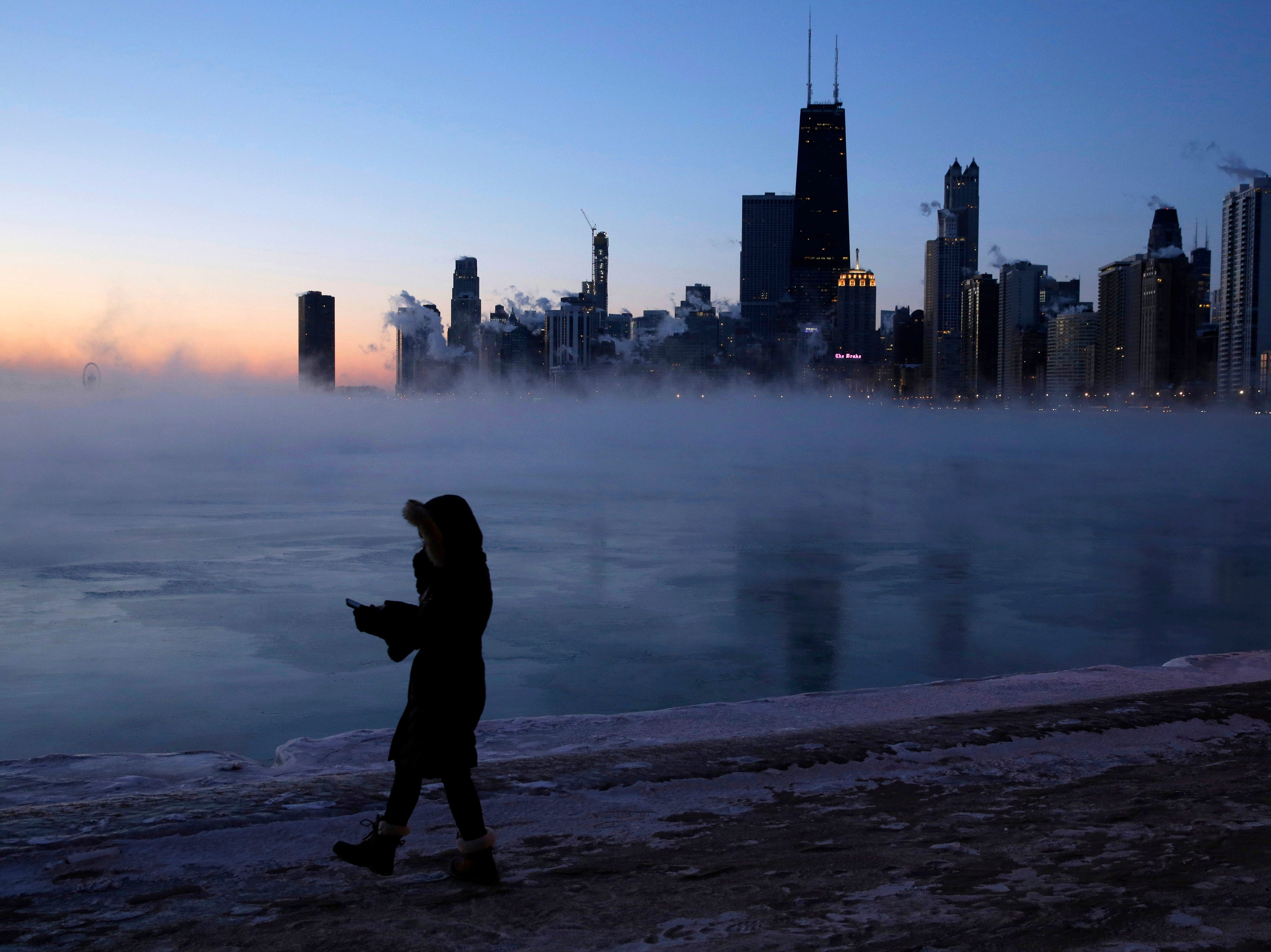A person walks along the lakeshore, Wednesday, Jan. 30, 2019, in Chicago. A deadly arctic deep freeze enveloped the Midwest with record-breaking temperatures, triggering widespread closures of schools and businesses, and prompting the U.S. Postal Service to take the rare step of suspending mail delivery to a wide swath of the region.