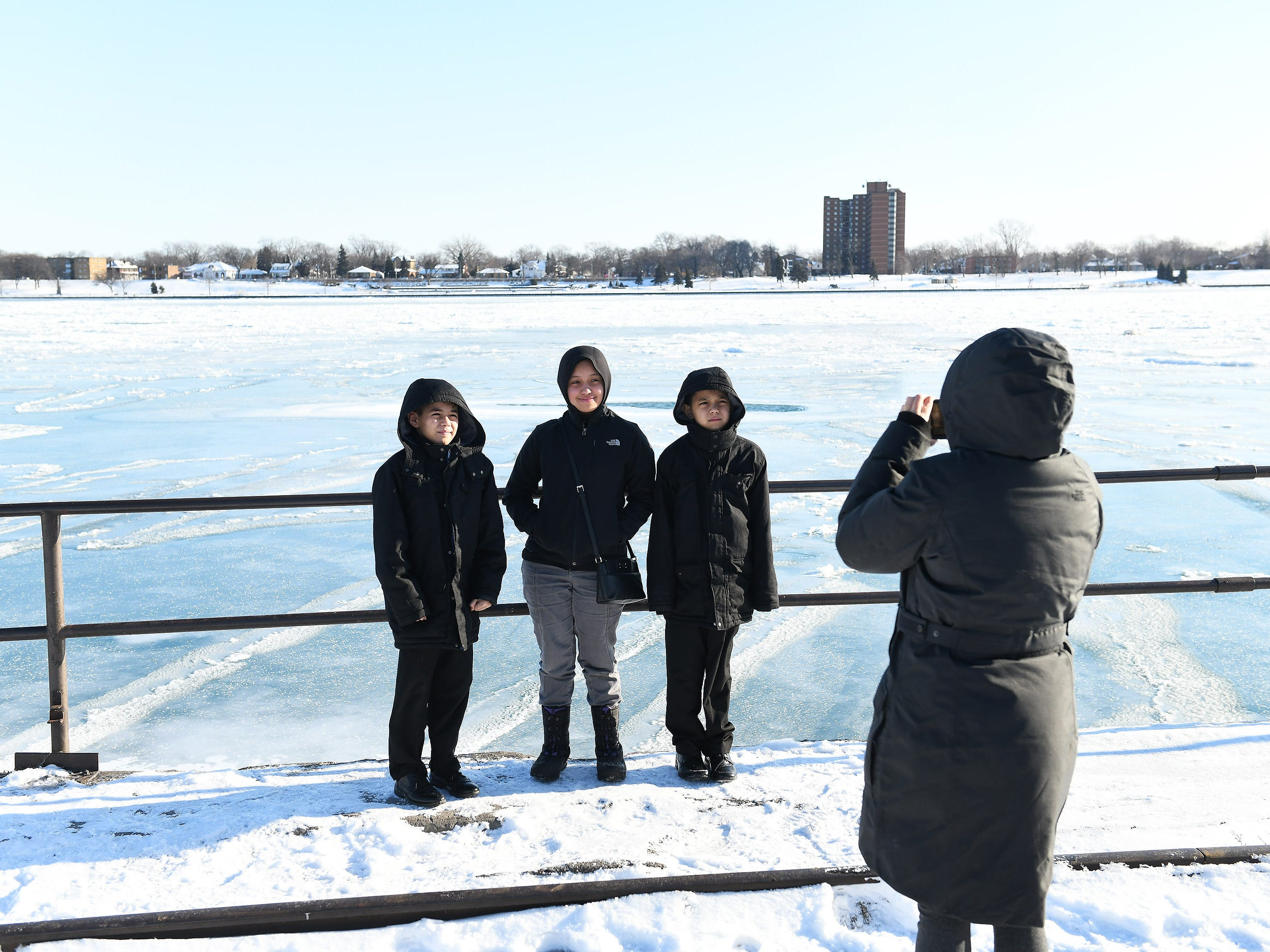 Gloria Santillan of Detroit takes photos of her children in front of the mostly frozen Detroit River.  They are, from left, Mattius Santillan, 10, Arabelle Santillan, 13, and Joaquin Santillan, 8. Santillan, who homeschools her children, says they often come down to the river.