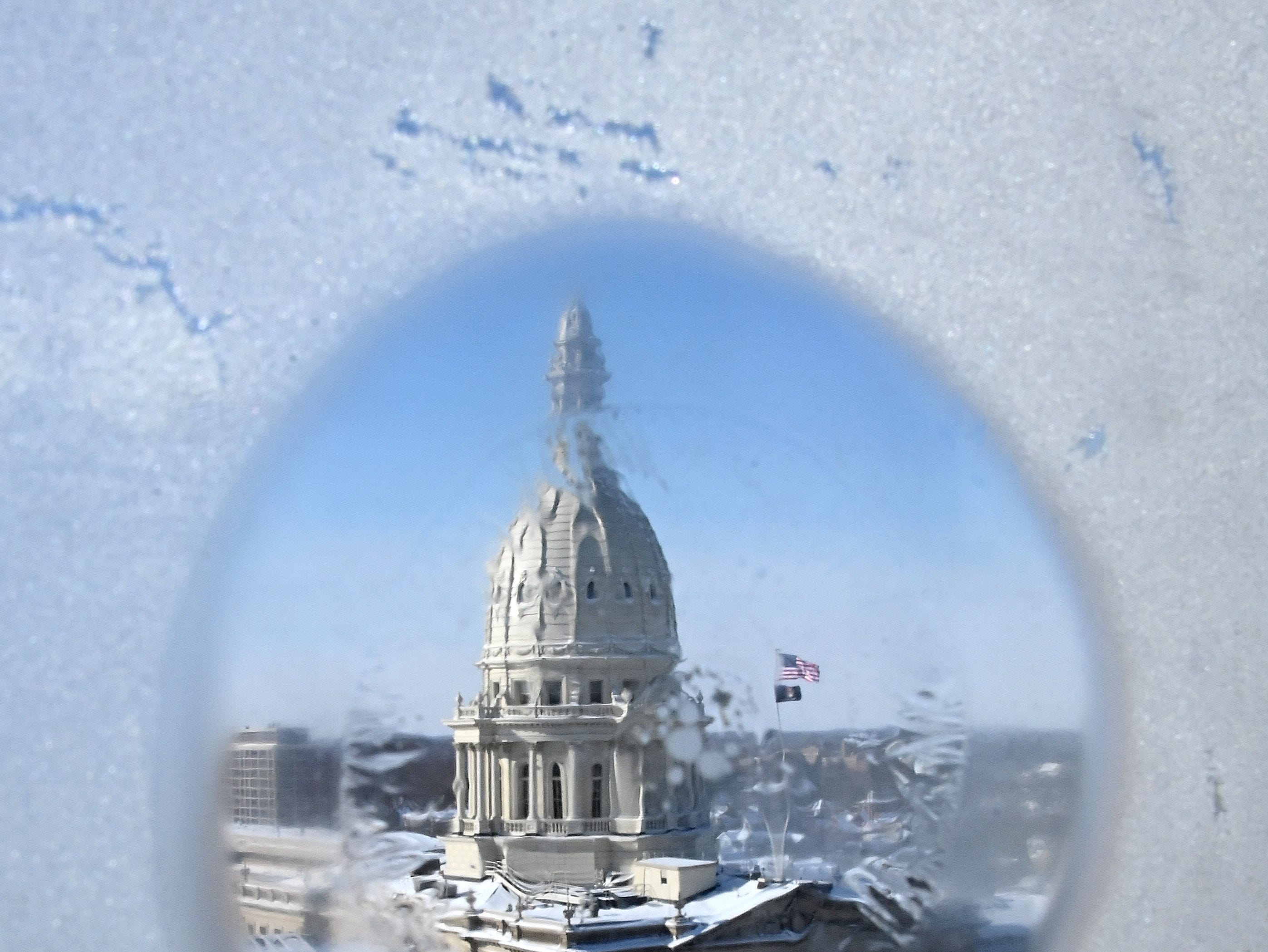 The Michigan Capitol building sits idle after extreme cold weather (minus 27 degrees counting the wind chill) prompted a governmental shutdown until Friday.  Here, the Capitol is seen through a frost-coated window in the Lansing bureau of The Detroit News on Wednesday afternoon, Jan. 30, 2019