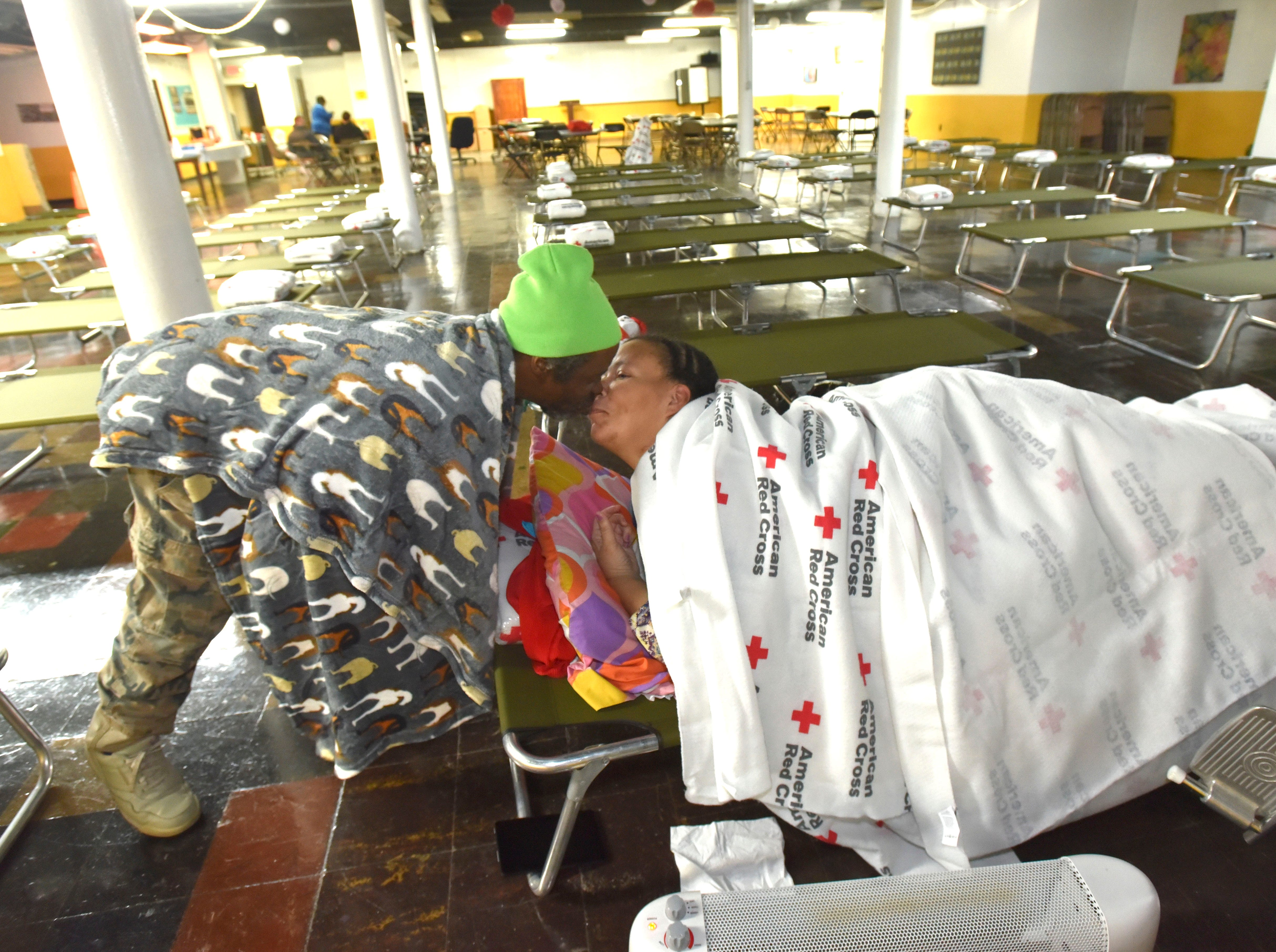 Anton Maurice Spann Sr., 56, gives wife, Shavonne Spann, 33, both of Detroit, a good-morning kiss Wednesday, Jan. 30, 2019. They were the only people to stay at the St. Augustine / St. Monica Catholic Church warming center Tuesday night. The Michigan Region of The American Red Cross has provided 50 cots for people needing the warming center, that is open 24 hours a day until Friday at 8 a.m. Personal necessity items and warm food is also available. Anton and Shavonne, his wife of 15 years, live close by in a two-family flat they rent for $400 per month. Their electricity bill is also $400 a month and they can't afford both, so Anton turned off the electricity and will stay at the warming center so they can pay both bills in the future.