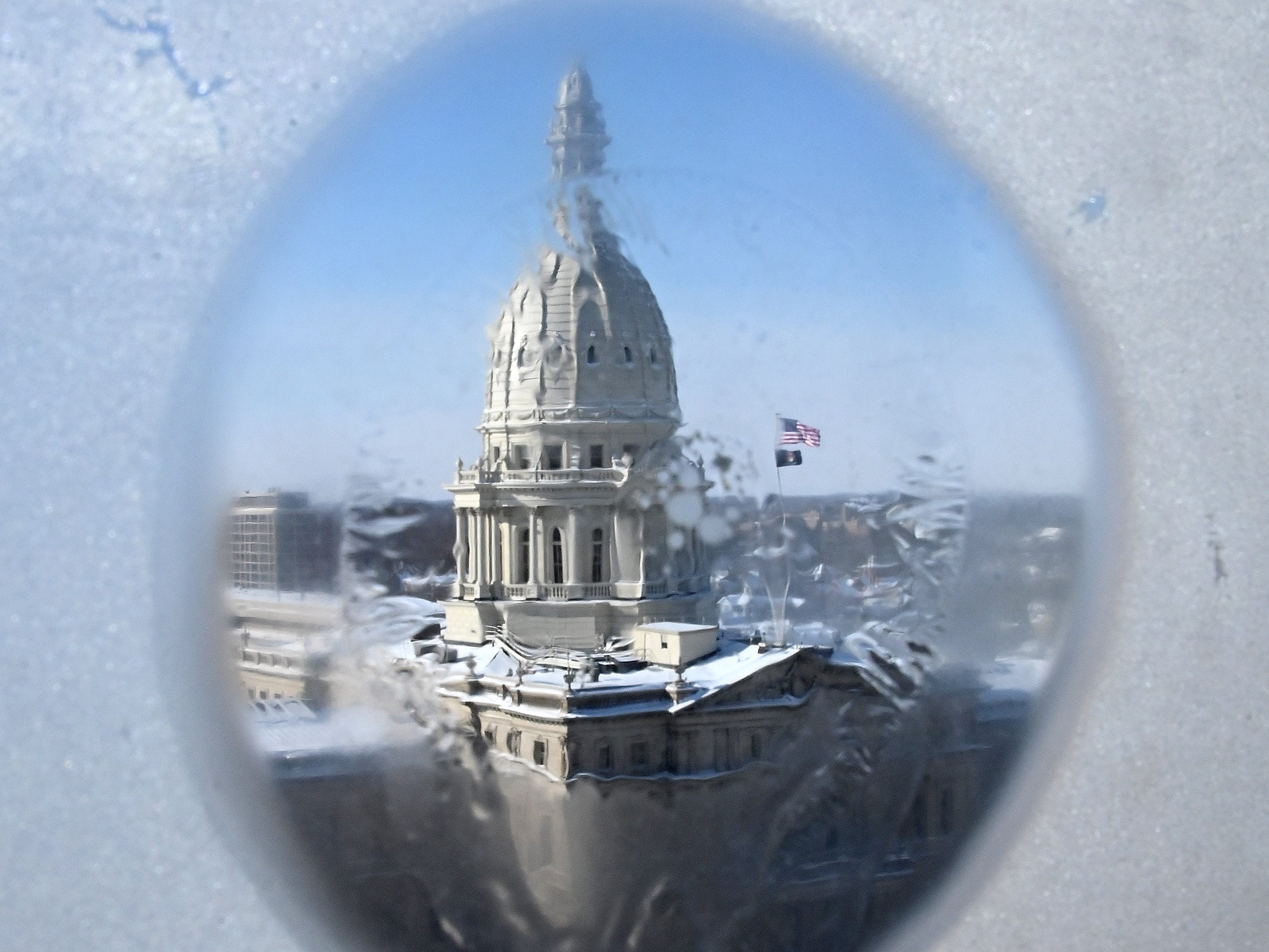 The Capitol building, seen through a frozen window in the Lansing bureau of The Detroit News, sits idle after extreme cold weather prompted a governmental shutdown until Friday.
