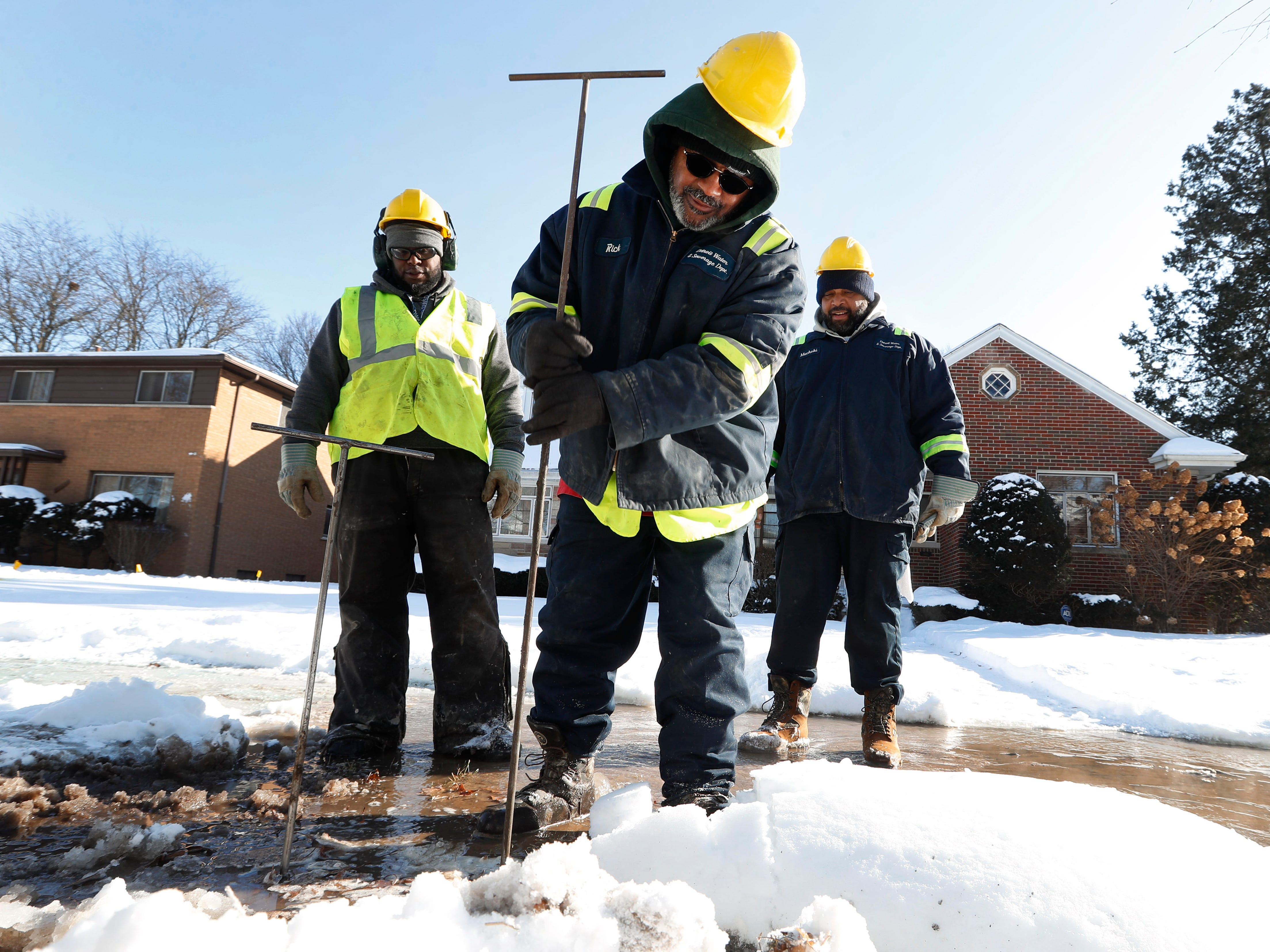 Richard James, a Detroit Water and Sewerage worker, uses a poking rod to find a water main break in Detroit, Wednesday.