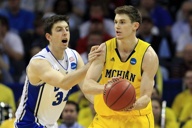 Michigan's Stu Douglass, right, is guarded by Duke's Ryan Kelly during the third round of the 2011 NCAA men's basketball tournament at Time Warner Cable Arena in Charlotte, North Carolina.