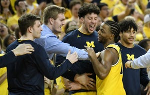 Michigan guard Zavier Simpson is congratulated by the Michigan bench as he exits the game with a triple-double.