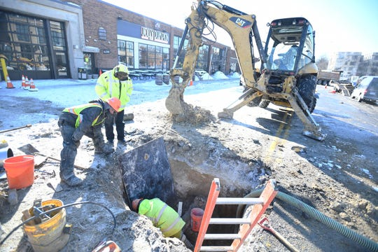 "Employees of Major Cement of Detroit work on a water main break Wednesday on Canfield between Cass and Second in Detroit. ""It's just too cold out here,"" said Jeff Jackson, superintendent of Major Cement. ""Get home, get warm and start all over again tomorrow."""