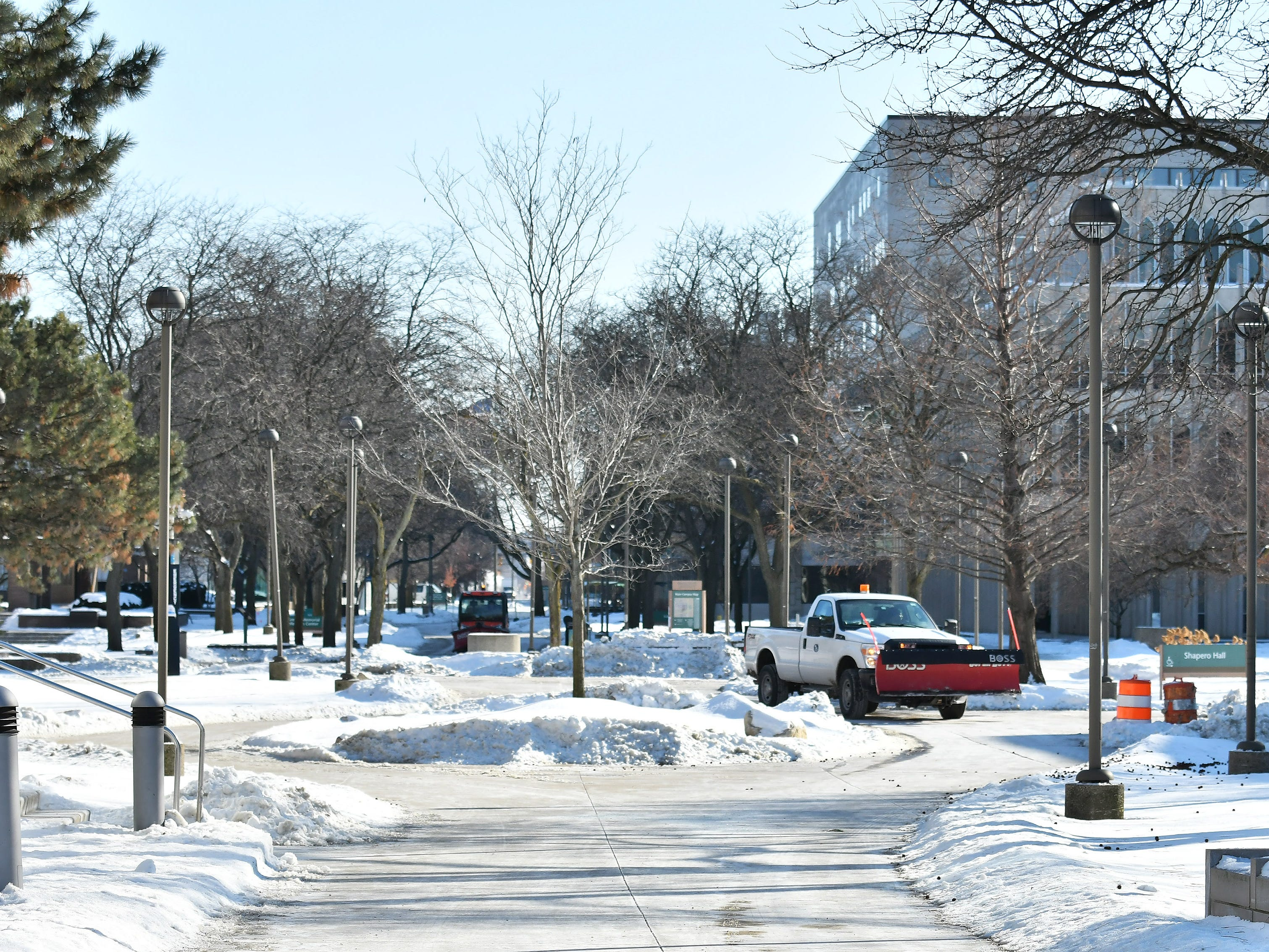 Maintenance vehicles drive on an empty walkway on the Wayne State University campus, where classes were canceled because of the severe cold.