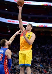 Bucks' Brook Lopez scores over Pistons' Blake Griffin in the first quarter.