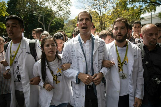 Opposition National Assembly President Juan Guaido, who declared himself interim president of Venezuela, takes part in a walk out against President Nicolas Maduro, in Caracas, Venezuela, Wednesday, Jan. 30, 2019.
