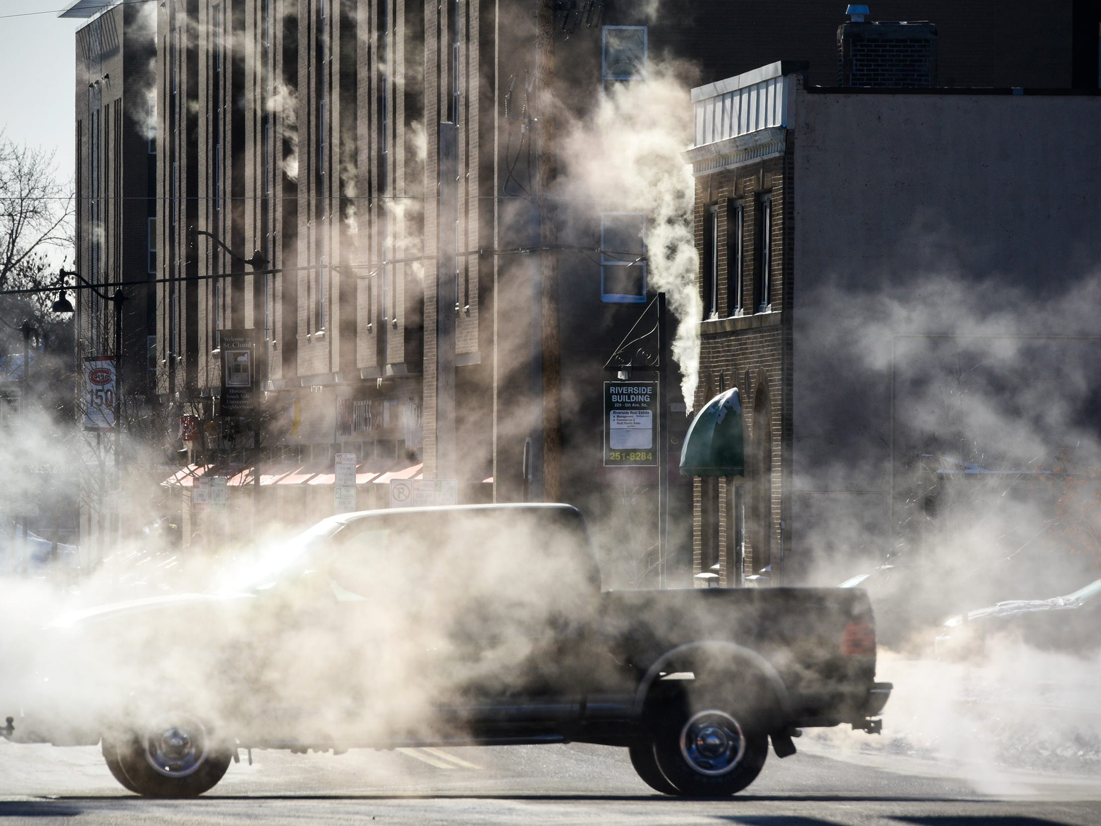 Morning sunlight highlights steam and exhaust as traffic travels along Minnesota Highway 23 near the intersection with Fifth Avenue South Wednesday, Jan. 30, 2019, in St. Cloud, Minn. Morning temperatures hovered around minus 30.