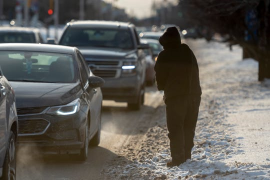A homeless woman panhandles on Warren Avenue in Detroit. on Tuesday. The expected temperatures will raise the frostbite risk.