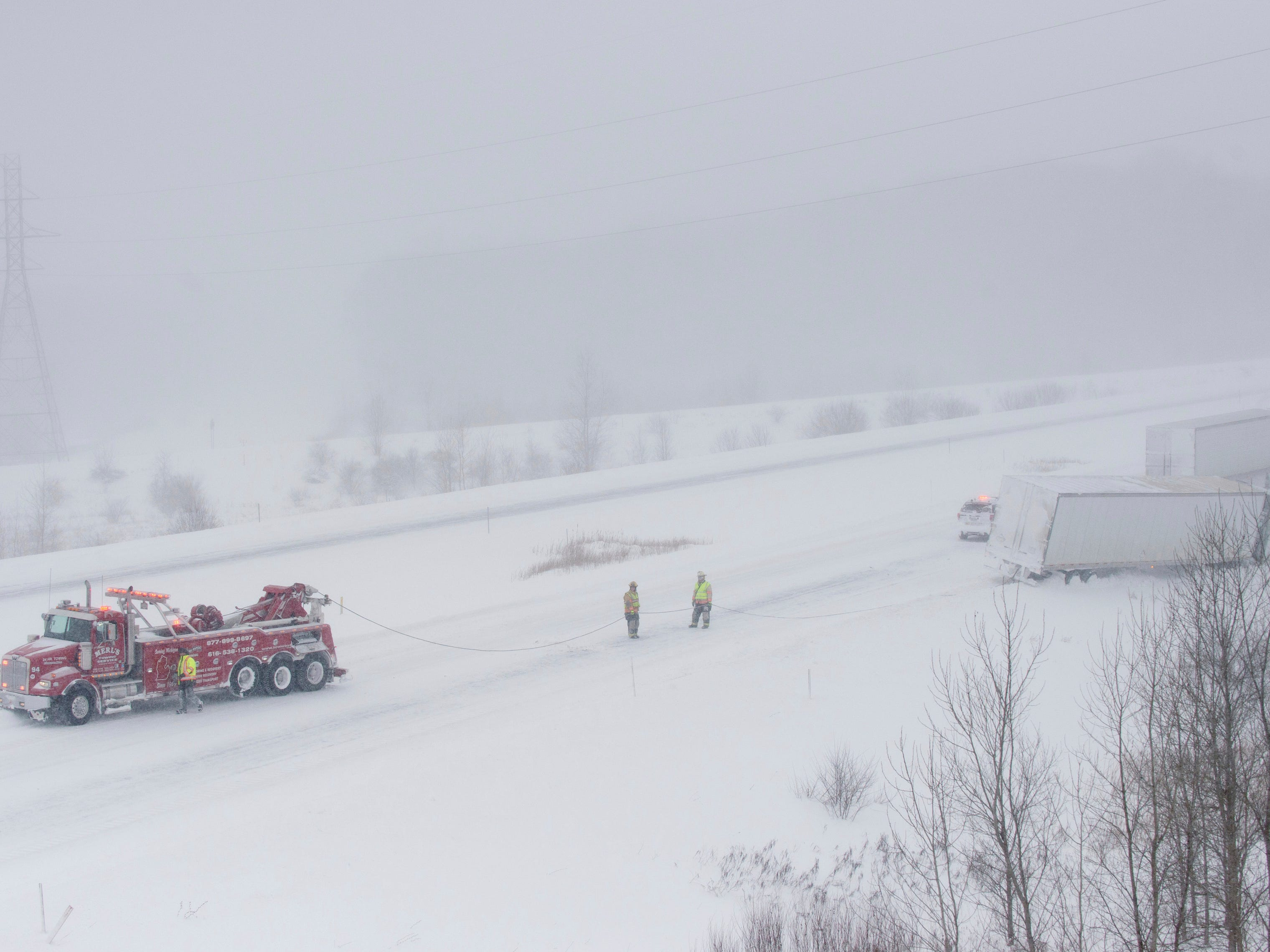 A Merl's Towing Service truck pulls a semi-trailer truck out of the snow Wednesday along M-6 near exit 1 outside Grandville.