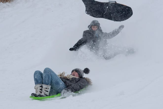 Children fly down the sledding hill at Heritage Park in Farmington Hills on Monday after school was called off.
