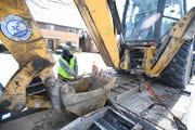 Miquel Cook, 21, a Detroit Water and Sewerage Department employee, straps down heavy equipment after working on a water main break on Renfrew in Detroit, Wednesday.