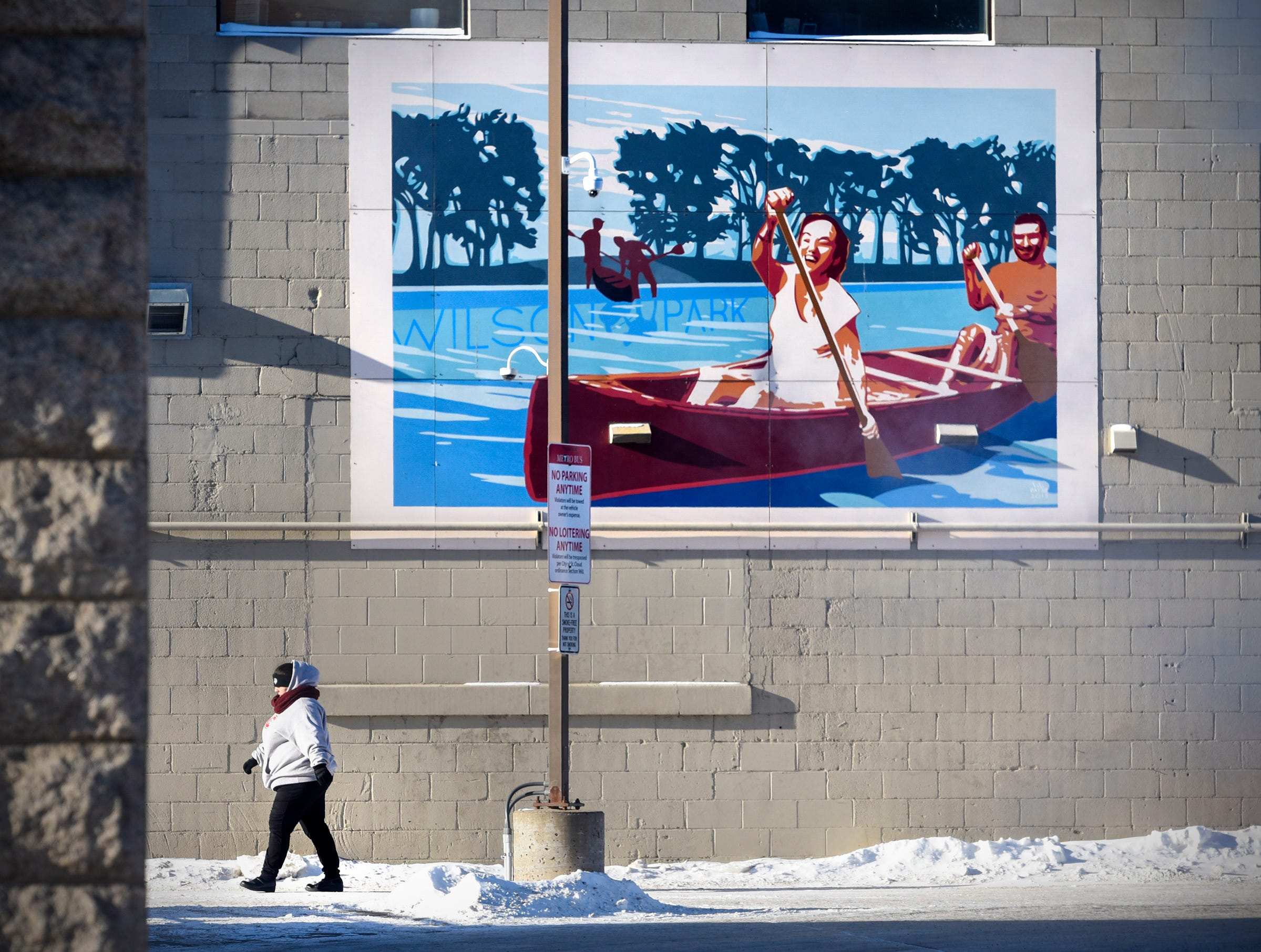A woman walks past a mural near the Metro Bus Transit Center Wednesday, Jan. 30, 2019, in downtown St. Cloud, Minn. Morning temperatures in the area were in the minus 30 range.
