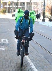 Theron Dillard delivers for Seven Greens restaurant on his bike in downtown Detroit, which was experiencing record cold weather on Wednesday.