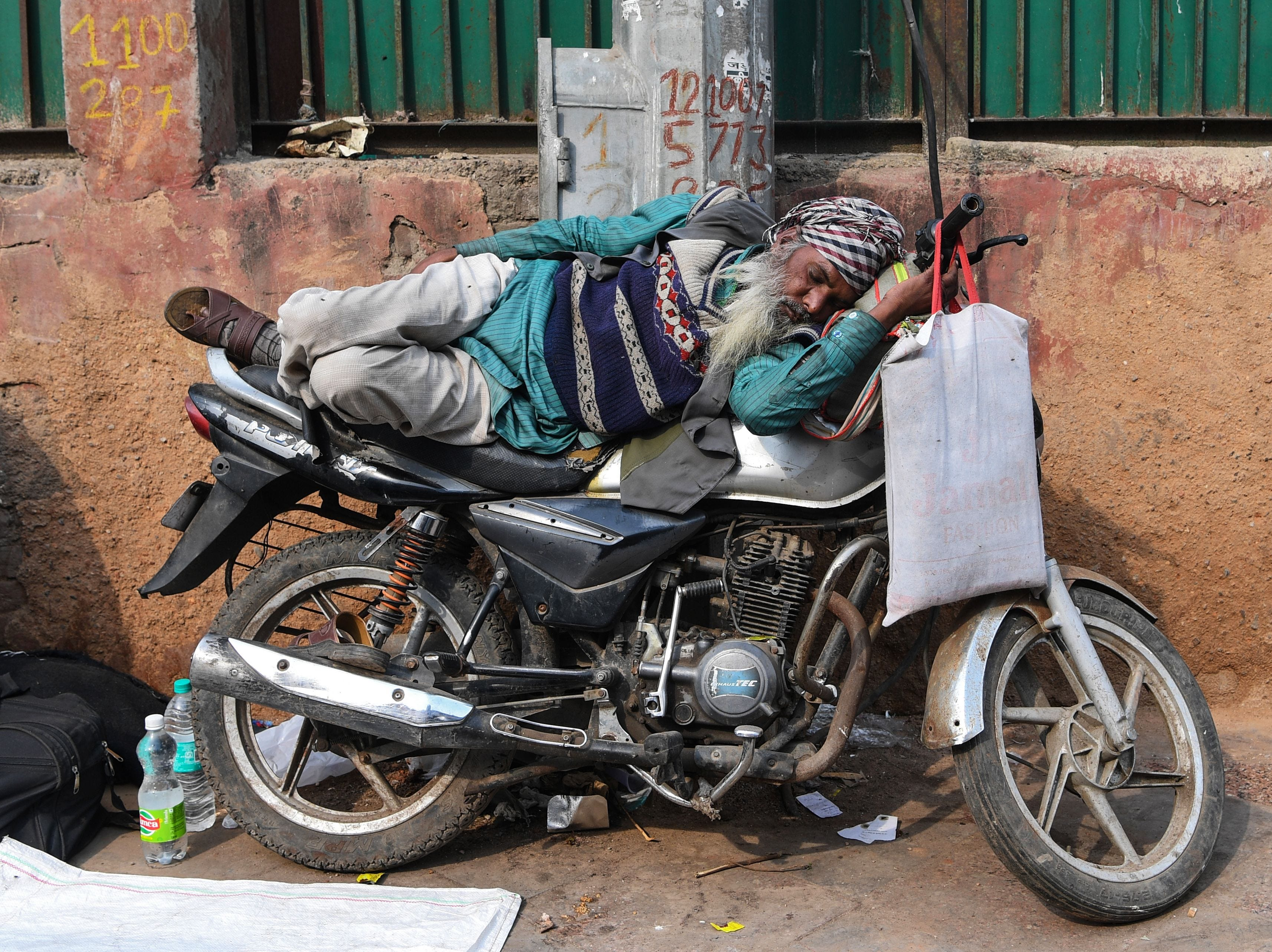 A man sleeps on a motorbike in the old quarters of New Delhi on Wednesday, Jan. 30, 2019.